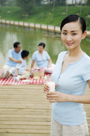 picnicking: Woman holding a glass of milk, family members picnicking in the background