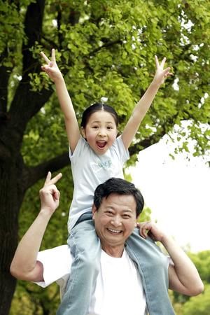 carrying girl: Senior man carrying girl on his shoulder LANG_EVOIMAGES