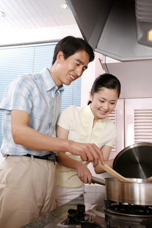 check ups: Mature man and woman cooking in the kitchen LANG_EVOIMAGES