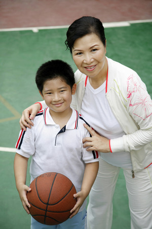 he   my sister: Boy with basketball posing with senior woman LANG_EVOIMAGES