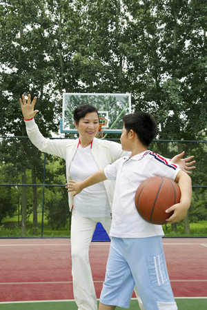 channel surfing: Boy playing  basketball with senior woman