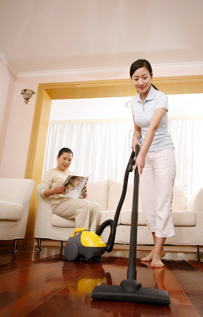 he   my sister: Woman vacuuming the floor with senior woman reading magazine LANG_EVOIMAGES