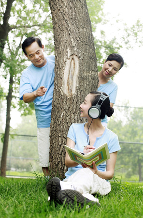 he   my sister: Woman listening to music on the headphones while writing diary, senior man and woman peeking from behind the tree