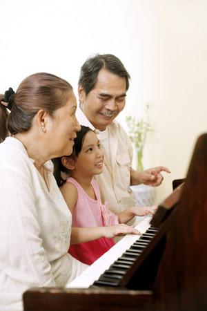 年配の男性と少女とピアノを弾く女性