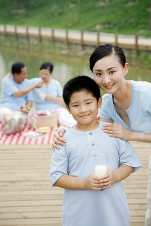 he   my sister: Woman and boy smiling at the camera, senior man and woman picnicking in the background LANG_EVOIMAGES