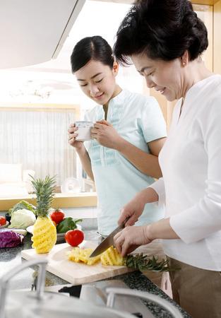 jubilating: Mature woman cutting pineapple, another woman watching