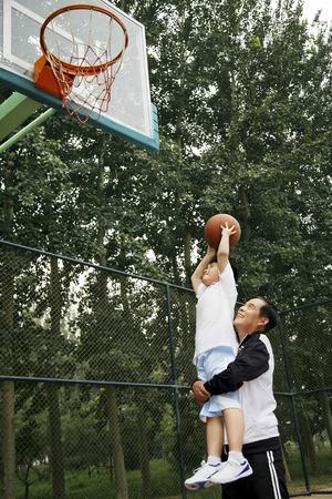 フープに、バスケット ボールを投げるしようとして年配の男性によって行われている少年