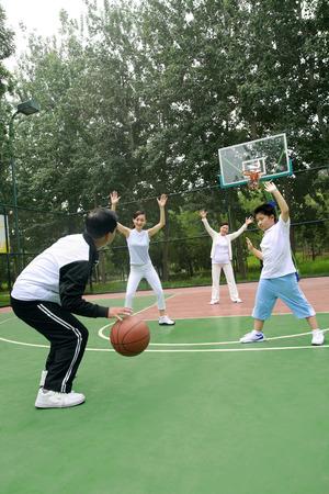 recreational sport: Family playing basketball together