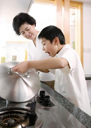 女性と台所の少年 写真素材