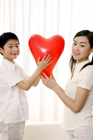 grandkid: Woman and boy posing with a heart shaped balloon