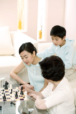 he   my sister: Boy watching women playing chess game at home LANG_EVOIMAGES