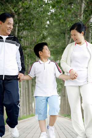 he   my sister: Senior man and woman holding boys hands while walking in the park