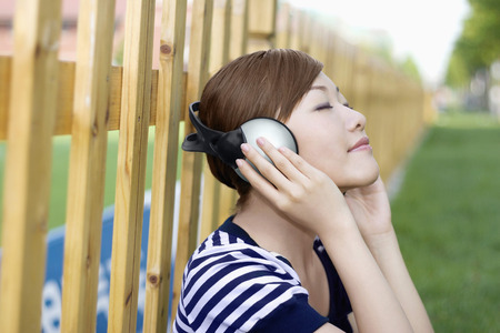 eyes closing: Woman closing her eyes while listening to music on headphones