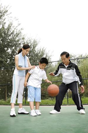 dribbling: Boy dribbling basketball, woman and senior man watching
