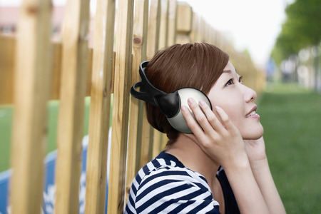 vintage: Woman with headphones listening to music while leaning against the fence