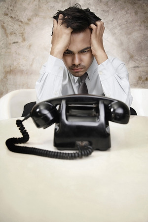 businessman waiting call: Businessman with head in hands waiting for a phone call