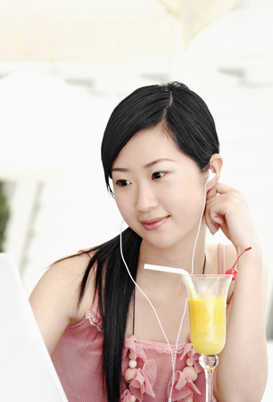 contentment: Woman listening to MP3 while using laptop LANG_EVOIMAGES