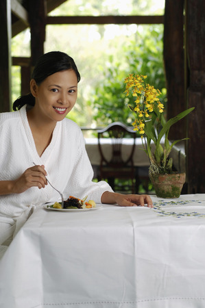 Woman in bathrobe eating salad