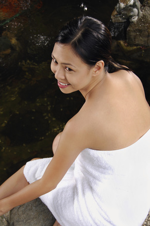 Woman in towel sitting by the pond LANG_EVOIMAGES