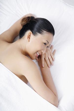 lying forward: Woman lying forward on massage table, smiling