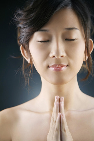clasping: Woman closing her eyes and clasping her hands LANG_EVOIMAGES