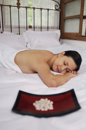 lying forward: Woman lying forward on bed with her eyes closed