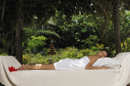 lying forward: Woman in towel lying forward on lounge chair LANG_EVOIMAGES