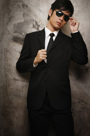 formal wear clothing: Businessman wearing sunglasses posing for the camera LANG_EVOIMAGES