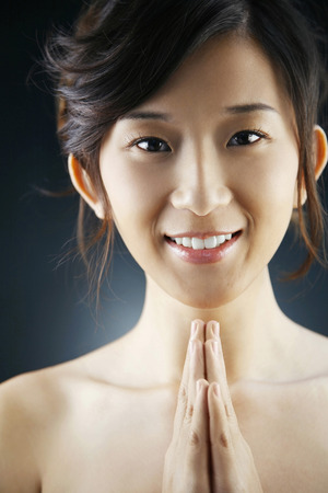 clasping: Woman smiling and clasping her hands LANG_EVOIMAGES