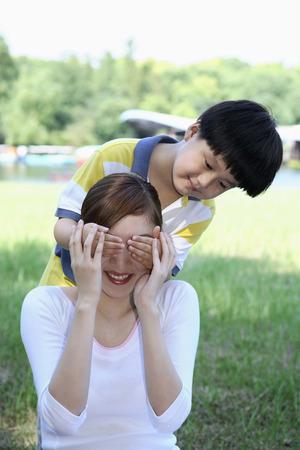 hands covering eyes: Boy covering womans eyes with both hands LANG_EVOIMAGES