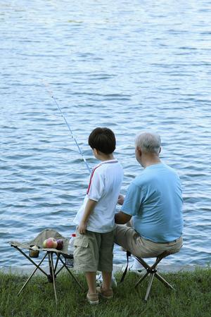 Senior man and boy fishing at the lake Stock Photo