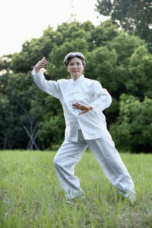 practising: Woman practising Tai Chi in the park