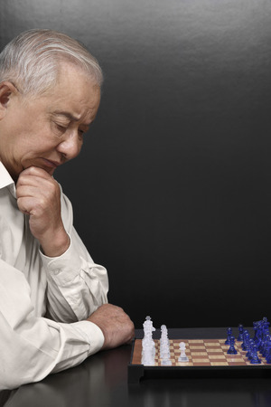 move in: Senior man contemplating on his next move in chess game LANG_EVOIMAGES