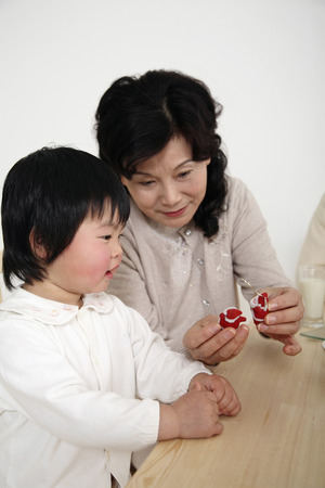 decorative item: Senior woman showing some christmas ornament to girl