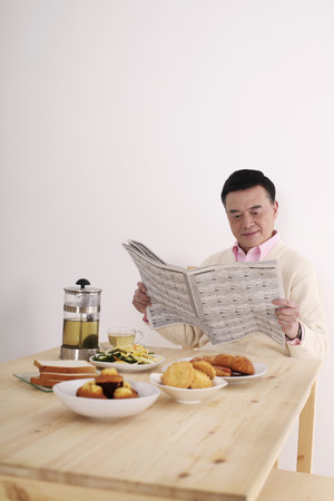 french ethnicity: Senior man reading newspaper while having breakfast