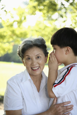 whispering: Boy whispering to senior woman