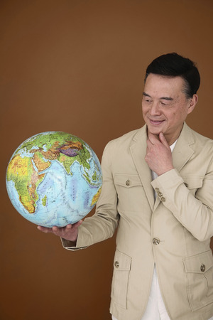 Senior man holding globe, rubbing chin while observing it