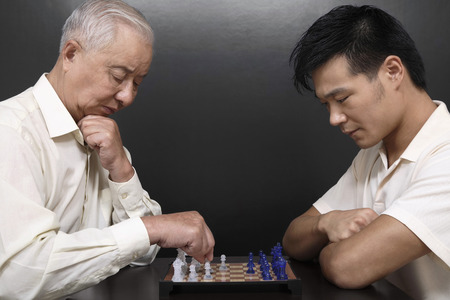 two people only: Senior man and man playing chess game