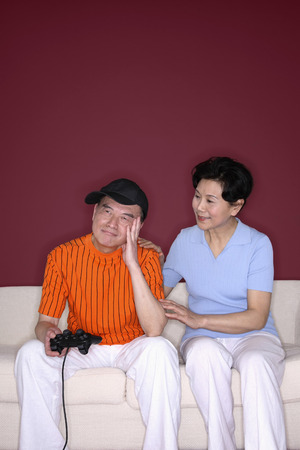 consoling: Senior man sulking after losing the game, senior woman consoling him LANG_EVOIMAGES