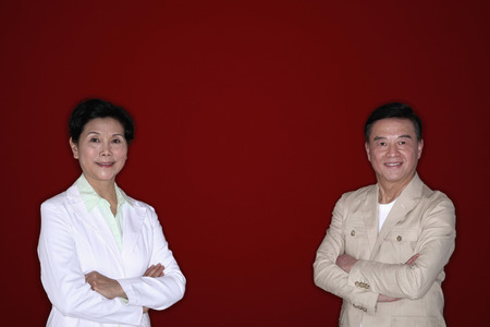 arms folded: Senior man and senior woman posing with their arms folded LANG_EVOIMAGES