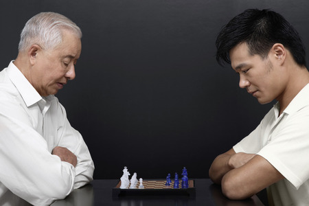 only mid adult men: Senior man and man playing chess