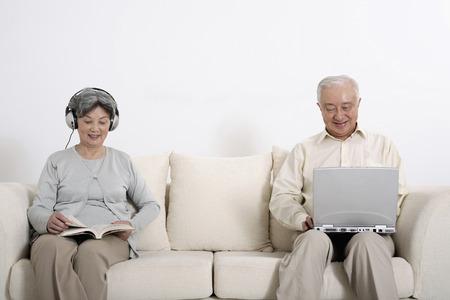 Senior woman listening to headphones while reading, senior man using laptop