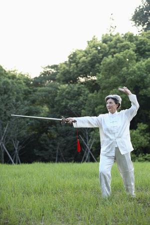 practising: Woman practising Tai Chi with sword