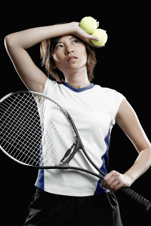 tennis racquet: Woman with tennis racquet and tennis ball wiping her sweat LANG_EVOIMAGES