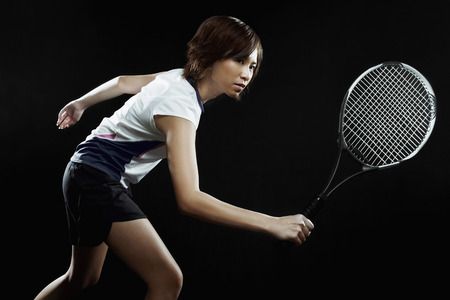 tennis racquet: Woman with tennis racquet preparing to hit LANG_EVOIMAGES