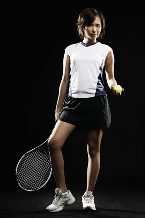 tennis racquet: Woman with tennis racquet and tennis ball posing for the camera