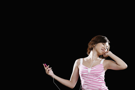 portable mp3 player: Woman listening to music on portable MP3 player