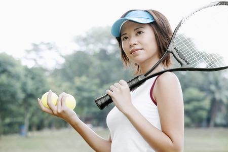 tennis racquet: Woman holding tennis racquet and tennis balls