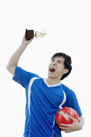 low prizes: Man screaming while holding trophy in air LANG_EVOIMAGES