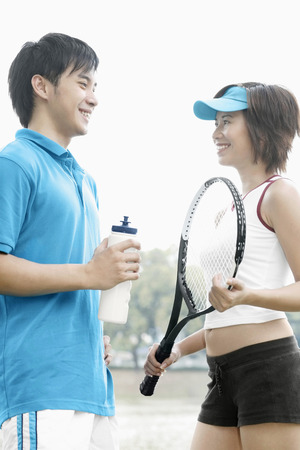 tennis racquet: Woman with tennis racquet talking to man LANG_EVOIMAGES